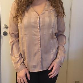 Blusen mangler den nederste knap, ellers helt uden brugstegn