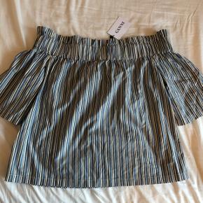 Off-shoulder bluse fra Ganni, størrelse L. Aldrig brugt, stadigvæk med prismærke. Kan afhentes på Frederiksberg eller sendes