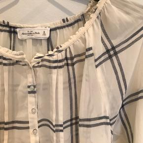 Transparent/beige skjorte fra A&F, med knapper og en smule pufærmer. Skjorten er brugt og har et lille utydeligt hul foran, som man ser hvis man ved det og står tæt på. Derfor standen slidt. Ellers er der ikke andet slidtage og ekstra billeder kan sendes🌸