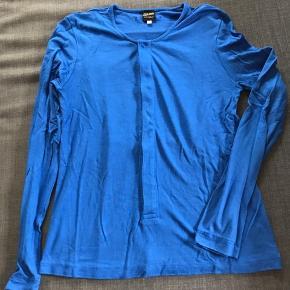 Supercool bluse fra Jean Paul Gaultier i flot blå farve med cool sort rygmærke og skjulte knapper foran (bortset fra den øverste😊). Str. S (lille i str.). Lidt slid, men ikke noget af betydning (pris sat derefter).