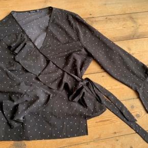 Jeg sælger denne fine slå-om bluse, med flæser og vige ærmer. Det er en størrelse 52. Den er aldrig brugt.  Den er ret lille i størrelsen.