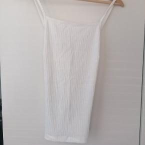 Hvid top med kryds-ryg og fri skuldre. Semi-tykt stof, ergo ikke see-through.