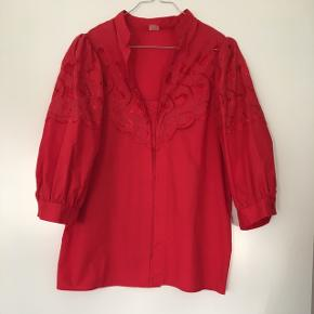 Postkasserød vintage t-shirt med blomsterbrodering og pufærmer i str m sælges. Den er i 65% polyester og 35% bomuld. Den har mange smukke detaljer og er i den flotteste stand.