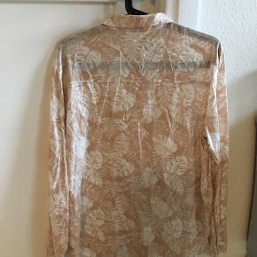 Lækker bomuldsskjorte i lysebrun med fine hvide blade. Har aldrig været brugt.