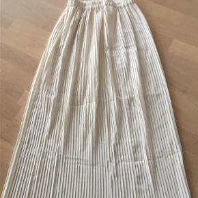 Brand: Paris Varetype: Plisseret nederdel Farve: Råhvid Oprindelig købspris: 599 kr. Prisen angivet er inklusiv forsendelse.  Lang plisseret nederdel - meget let model med elastik i taljen -  købt i Paris. Længde: 92 cm Talje: 2 x 31 cm - kan strækkes til 2 x 45 cm Har den samme i sort  Sælges et stk for 175,- . Dem begge for kr. 300,-