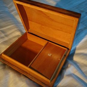 Gammel og velholdt smykkeskrin/spilledåse. Lille rum til venstre og spilledåse til højre under lille låg. Spiller automatisk når låget åbnes og kan trækkes op med nøgle i bunden. 17x13 cm