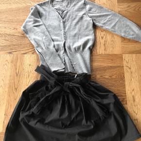 Nederdel - som ny - sort med bindebånd og elastik i taljen ( brugt een gang)  Str 10 år  Grå strik cardigan med uld fra Christina Rohde - max brugt 4 gange men enkelt knap mangler str 10