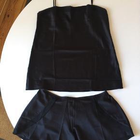 """Nattøjssæt fra Oysho med transparente detaljer ved lommer og langs overkanten af blusen og shorts på bagsiden. Aldrig brugt eller vasket, dog er mærket klippet af. """"Ligner"""" silke, men er det ikke."""