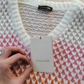 Smuk sweater fra Stine Goya,  Model: Jodi Sweater  Flerfarvet strik sweater med farverige striber i off white, pink, Peachy appelsin, lyseblå og mørk navy blå. Denne strik har lange ærmer, en V-udskæring og ribbet detaljer ved halsen, forneden og manchetter. Nypris 1600,-