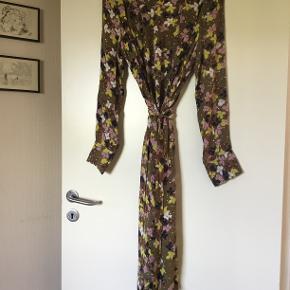 Lang kimono fra Vero Moda, khaki med blomster. Lange ærmer med manchetter der har 2 stofovertrukne knapper, der medfølger bindebånd. Fejlkøb.Aldrig brugt.