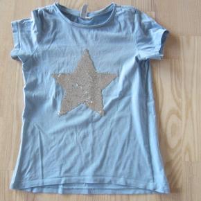 """STR. 134/140. Sød lyseblå t-shirt fra """"Friboo"""" med pailletstjerne på, som både kan være hvid og sølvfarvet. Der er et par små pletter foran,og enlille plet på ryggen, og så er den lidt skæv i syningen, men det er ikke noget man lægger mærke til, når den er i brug.  Porto: 37 kr. sendt som pakke uden omdeling med DAO.  Jeg har tøj til både baby, piger, drenge, kvinder og mænd i stort set alle størrelser. Send mig blot din mailadresse, og skriv hvilke størrelser du er interesseret i. Så sender jeg en mail retur med billeder/beskrivelser/priser."""