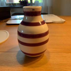 Hej! Jeg sælger denne fine Kahler vase. Den er i farven blomme lilla. Den er 13 cm høj. Der er ingen fejl på den, og ser faktisk helt ny ud, også i bunden. Jeg sælger den til 100 kr. Hvis du har nogle spørgsmål til vasen, så spørg løs.  Tjek gerne mine andre annoncer ud for en masse billige ting.