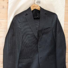 Virkelig flot jakkesæt fra Acne. 55% uld, 45% bomuld. Sort/koksgråt. Indvendig benlængde 70,5 cm. Livvidde 90 cm. Vidde ved anklerne 2 x 15,5 cm. Udvendig ærmelængde 67 cm. Fin stand. #30dayssellout