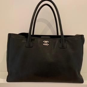 Elegant Chanel Cerf taske fra 2008. Perfekt som arbejdstaske eller blot, hvis man ønsker sig en unik Chanel taske med mere plads. Der er så mange gode rum (7 rum). Bl.a. en aftagelig clutch rumdeler, som kan tages op, hvis man ønsker et stort rum i tasken eller blot skal have nogle småting med sig. Til tasken medfølger også en rem, så den også kan bruges som crossbody.   Stand: Næsten som ny, kun brugt få gange som arbejdstaske   Farve: Sort læder med sølv hardware   Dustbag: Ja original dustbag   Seriekortnr: ja   Størrelse: L = 36, H = 24,5, B = 15