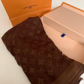 Sælger mit super fine Louis Vuitton tørklæde i brunt  Der medfølger pose og æske   Der er desværre kommet noget fnuller på det efter brug