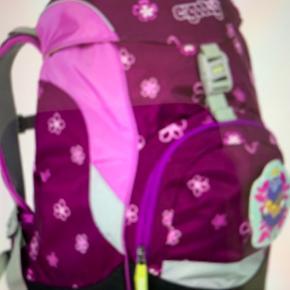 Skoletaske - Ergonomisk  Ergobag Prime Purpel Flowers  En taske i flot design med fokus på ergonomi.  Hos ergobag er ergonomien det allervigtigste, når de laver en ergobag skoletaske. Design er de heldigvis også supergode til. For at udvikle deres unikke rygsække og skoletasker har de kombineret viden om ergonomikonceptet fra innovative vandrerygsække med de mange krav, der stilles til en skoletaske i grundskoletiden. Resultatet er en taske, der skåner barnets ryg, selvom tunge bøger, madkasse og idrætstøj vejer godt til.  Betaling via mobilepay plus forsendelses.  Mærket på toppen følger ikke med.