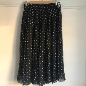Højtaljet nederdel i sort med hvide prikker.