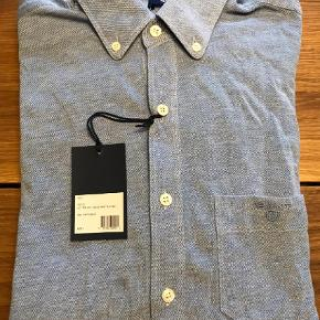 Varetype: Langærmet Farve: Lyseblå Oprindelig købspris: 900 kr.  Pique skjorte, i 100% bomuld. Føles som der er strech i, pga vævningen. Lidt Fitted.