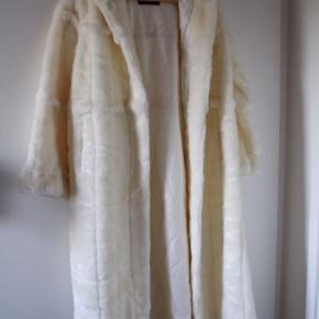 Elegant råhvid hellang faux fur med fine detaljer og hætte.  Lukkes med hægter som rigtig pels.  Str. L - ryglængde 125 cm. Aldrig brugt.  Køber betaler forsendelse.    Prisidé 2500kr - bud modtages også gerne.