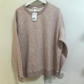 Let rosafarvet sweatshirt fra HM. Aldrig brugt og stadig med prismærke.