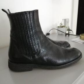 Klassisk støvle fra Angulus i blødt skind. Støvlerne har været brugt 1 sæson, og er stadig meget pæne. Støvlens pasform er til den smalle side. Jeg bruger normalt str 40, men har fint passet denne i str 39 1/2. Det er med rågummisåler. Nypris kr 1299.-