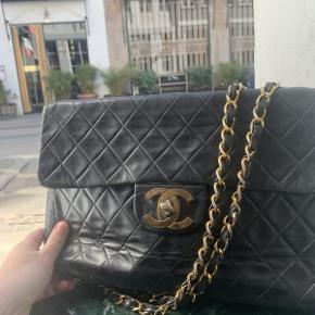 Vintage Chanel Maxi Jumbo i sort læder, med guldhardware.  Der medfølger ikke originalt købstilbehør til tasken.  Tasken fremstår i brugt vintage stand med brugsspor.  Låsen har slid, der er lidt slid på hjørnerne af tasken mm.  Tasken måler ca 34 x 23cm.