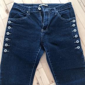 Fede Place du Jour jeans med knapper i siderne og masser af stretch.   Bukserne er størrelsessvarende.   Nypris 400 kr.   Køber betaler evt porto. Jeg sender med Dao.