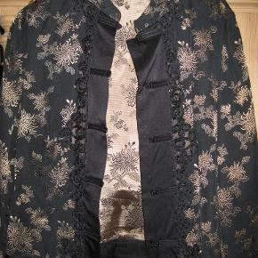 Smuk Kina-inspireret jakke i sort med guld, silke og viskose med gl.-dags. lukkemekanisme. Mål over bryst: 47 cm Længde: 55 cm  I fin stand og meget smuk.