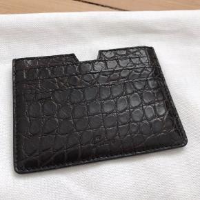 Super flot kvalitets kortholder fra det danske Graae Copenhagen.  Kortholderen er udført i mørkebrunt alligatorskind fra US.  Mål: 11 x 8 cm  Nypris 4050,- Kom gerne med et bud!