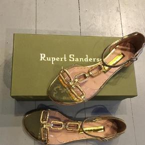 Smukke flade guldfarvede sandaler fra Rupert Sandersson i original æske.  Nypris 4700,-  Sandaler Farve: Guld Oprindelig købspris: 4700 kr.