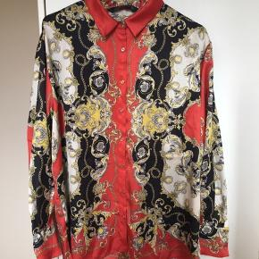 Mega fed skjorte fra Zara i super cool tørklædeprint med dekorative guldknapper og i enkelt let oversize snit. Stoffet er lidt skinnende og falder flot langs kroppen. Farverne er rød, sort, hvid og guld. Str. M, men passer flere str pga snittet. Kom med et bud. NP: 450kr.  Varen befinder sig i 9520 Skørping. Sender med DAO.  Se også min øvrige annoncer. Jeg sælger tøj, sko og accessories. Pt er min shop fuld af vintagekup, high street fund og mærkevarer i mange forskellige str. Kig forbi og spøg endelig!