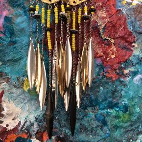 Boheme/indian style smukkeste unika perle-øreringe, lig mærke til de flotte metalfjer i guld, sølv og sort, smuk detalje der glimter når man har dem på, måler ca. 17 cm fra top til sort fjerspids. Brugt få gange.