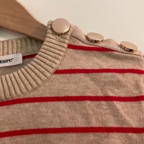Co'Coture strik med røde striber og fine knapper på den ene skulder.  Er brugt og vasket 1 gang. Som ny.