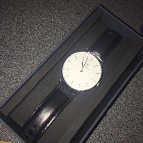 Super klassisk Daniel Wellington ur med sort læderrem  Brugt 3 gange  Kan sendes mod betaling   Æske medfølger