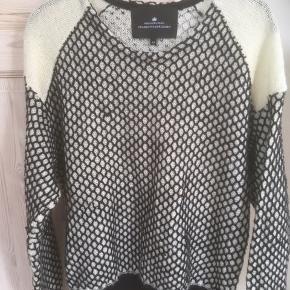 Mærke: Designers Remix Charlotte Eskildsen Style: Nanna, 96600 Størrelse: XS. Passer også str S evt M Farve: sort og råhvid Materiale: 66% Wool, 5% Mohair, 19% Acrylic, 10% Polyamide Blusen: længde 64 cm. Breden fra ærmegab til ærmegab 61 cm. En meget blød bluse Stand: brugt få gange  Sælges 350 kr