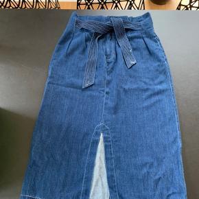 Denim nederdel, med lommer foran og bagved. Matchende bælte man binder.