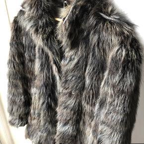 Den fedeste pelsjakke i flotte grå nuancer med læder- detaljer ved skuldre, åbning og lommer. Den er så flot!