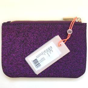 Perfekt stand, aldrig brugt.  Flot glimtende materiale og praktisk størrelse, perfekt til at have med i tasken enten som pung eller som kosmetikpung etc.   Nypris: 250,-