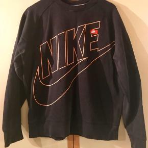 Behagelig sweatshirts fra Nike med stort print for sælges da det skal ryddes ud i skabet. Trøjen er brugt men fremstår helt fint, uden nogen forme for pletter, huller el. Fremstillet i kraftigt blødt stof med god kvalitet på printet for.  Giv et bud