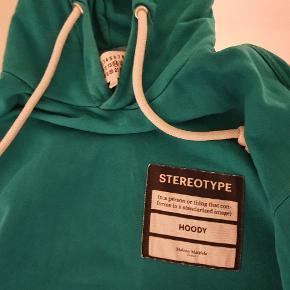 Denne fede Maison Margiela hoodie er købt på vestiare collective Trøjen er XL, men stort. Ny pris var på omkring 3000 Min pris er 650, da trøjen er godt brugt har intet OG, men den er autentisk og er blevet godkendt fra vestiares legit check system. Trøjen har 2 flaws, skriv en besked og jeg sender billeder af dem. Det ene flaw er nederst på ryggen og det andet er i pouchen.  Ellers en ganske dejlig hoodie.
