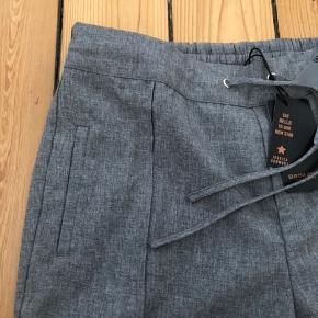 Pæne bukser i tyndt, let materiale i light grey melange, perfekt til sommeren.  Nypris kr 329, købt for kr 100 på udsalg.  Elastik og bindebånd i taljen, lommer foran og snydelommer bagpå.   Kan sendes eller afhentes i Rødovre.