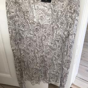 Hvid med brunt mønster, 100 % silke. Tynd, let og luftig, bytter ikke.