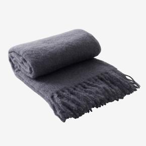 Eksklusiv plaid i mohair og uld med frynser i enderne. Plaiden er mørkeblå og kvaliteten er luksuriøs med en stor andel mohair, som er en let og fin type uld fra angorageden.  70% mohair, 30% uld og 5% polyamid. Størrelse: 130x170 cm Vaskeanvisning: Kemisk rens.  P R I S   4 5 0,-  (i butikken 1.600,-) Helt ny og i ubrudt emballage.  Har 2 stk i mørkeblå og 2 stk i lysegrå.