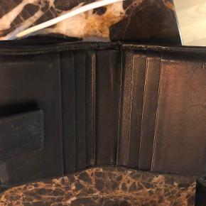 Gucci pung med masser af plads til kort, mønter og sedler. Pungen er efterhånden nogle år gammel, men stadig super fin, dog lidt slidt på kanterne. Selve læderet er stadig fint og blødt. Pungen kan ses og afhentes i Kbh. SV/Valby.