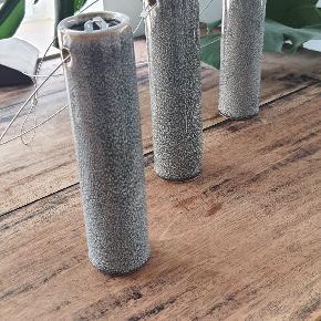 Cylinderformet hængevaser i glaseret keramik med stål wire.   16 cm. Høj 4 cm. I diameter.  40 kr. Pr. Stk eller alle 3 for 100 kr.