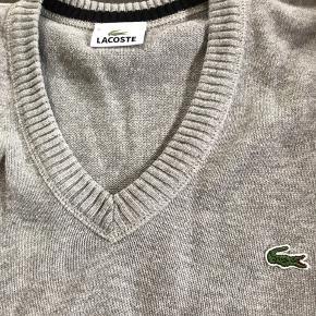 Superflot v-hals sweater fra Lacoste i fin lysegrå farve uden huller eller synlige tegn på slid. Str. L (men lidt stor).