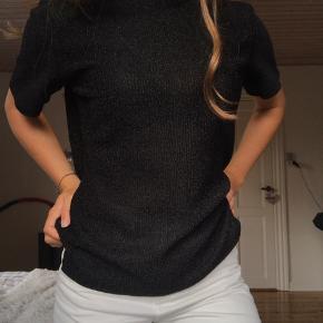 Sort glimmer Envii t-shirt som er en smule gennemsigtig. Blusen er str. L men ville passe en str. S eller M og bare sidde lidt mere løst.