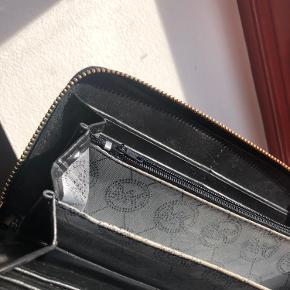 Stor og sort MK pung❤️  Købt brugt men for ikke brugt den❤️  ❌ Bukstaverne er en lillesmule slidt men ikke noget man ligger mærke til