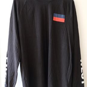 Flot langærmet t-shirt i 100% bomuld. Skriften på ærmer vender bagud/udad når man har den på.