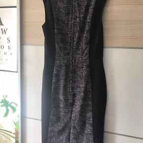 Flot bodycon kjole, med flot panel.  Giver en flot figur, sælges da den desværre ikke bliver brugt længere.   Lang lynlås bagpå og slids.  Går mig cirka til lige over knæet (er 171 cm)
